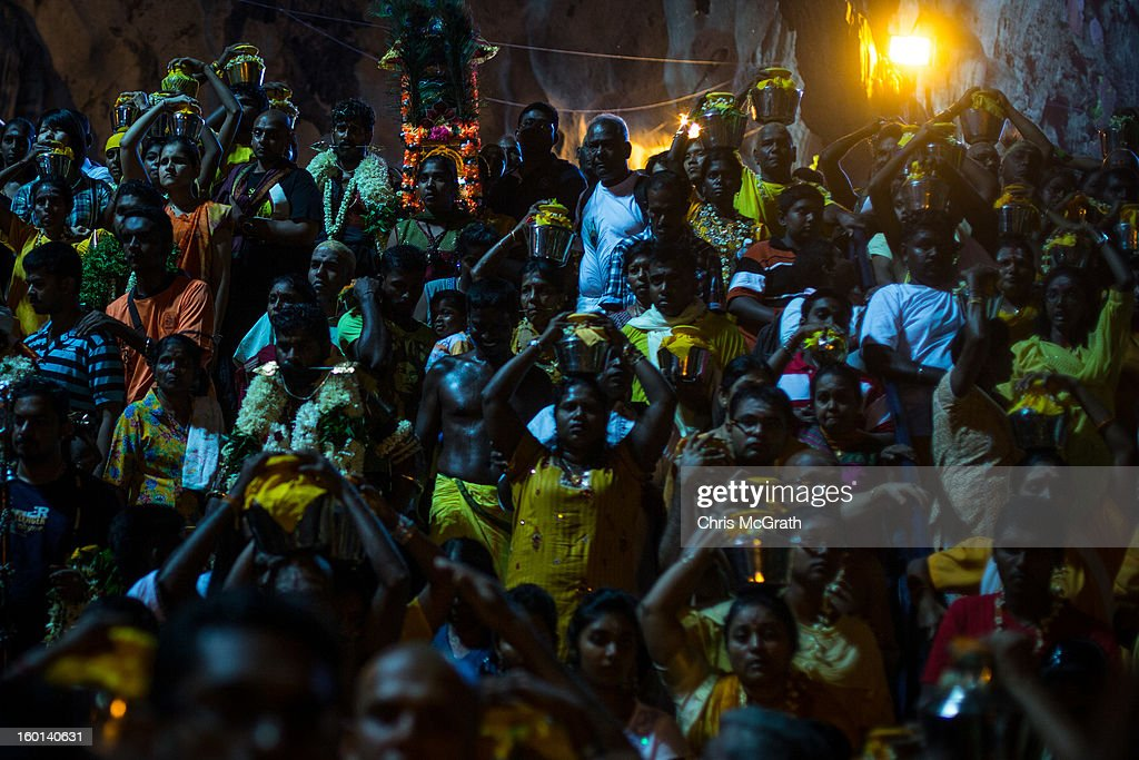 Devotees carrying heavy pots of milk make their way through the entrance of the Batu Caves during the Thaipusam procession on January 27, 2013 in Batu Caves, Malaysia. Thaipusam is a Hindu festival celebrated on the full moon in the Tamil month of Thai. The festival marks the birthday of Lord Muruga and also commemorates the day Hindu Goddess Parvati gave her son a lance to defeat the evil demon Soorapadamwhen. The festival sees devotees carry milk pots to seek forgivness and some will carry a 'Kavadi' many of which are attached via, strings, hooks, and skews pierced into the carriers skin.