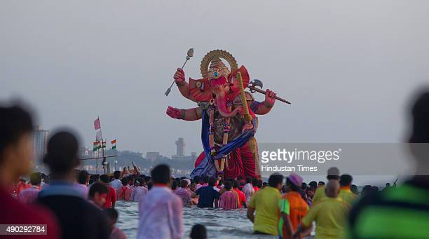 Devotees carrying idols of Hindu Lord Ganesha to immerse in river on the last day of the Ganesh Chaturthi festival at Girgaon Chowpatty on September...