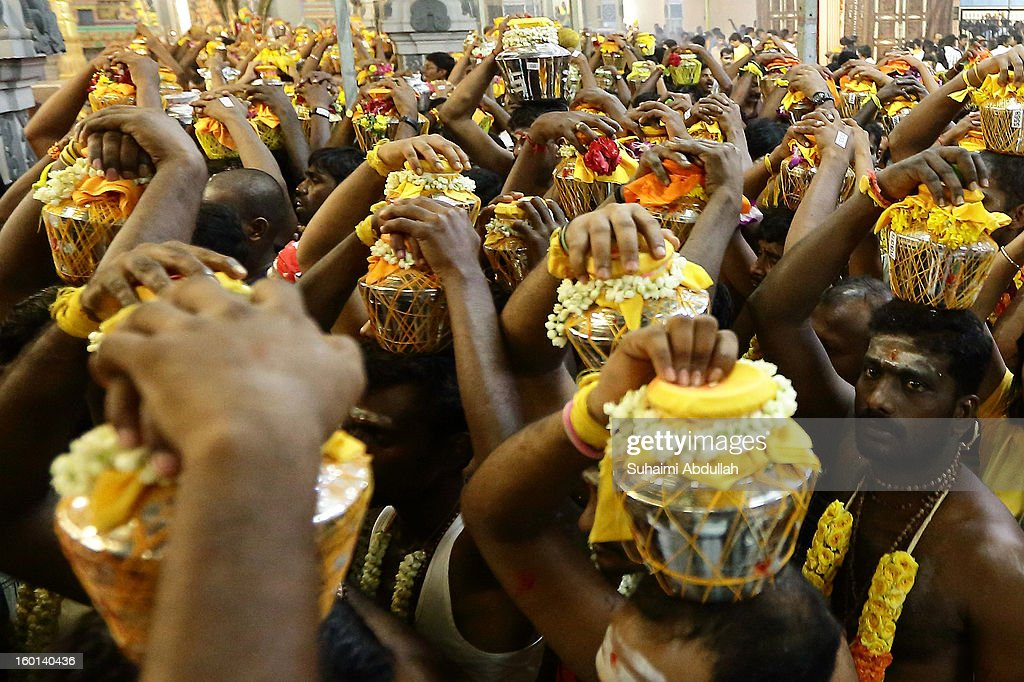 Devotees carrying milk pots prepare to leave the temple ground to begin their Thaipusam procession at Sri Srinivasa Perumal Temple on January 27, 2013 in Singapore. Thaipusam is a Hindu festival celebrated on the full moon in the Tamil month of Thai. Devotees pray and make vows, when the prayers are answered they fulfill the vows by piercing parts of their body such as their cheeks, tongues, and backs before carrying a 'Kavadi' along a four kilometre route.