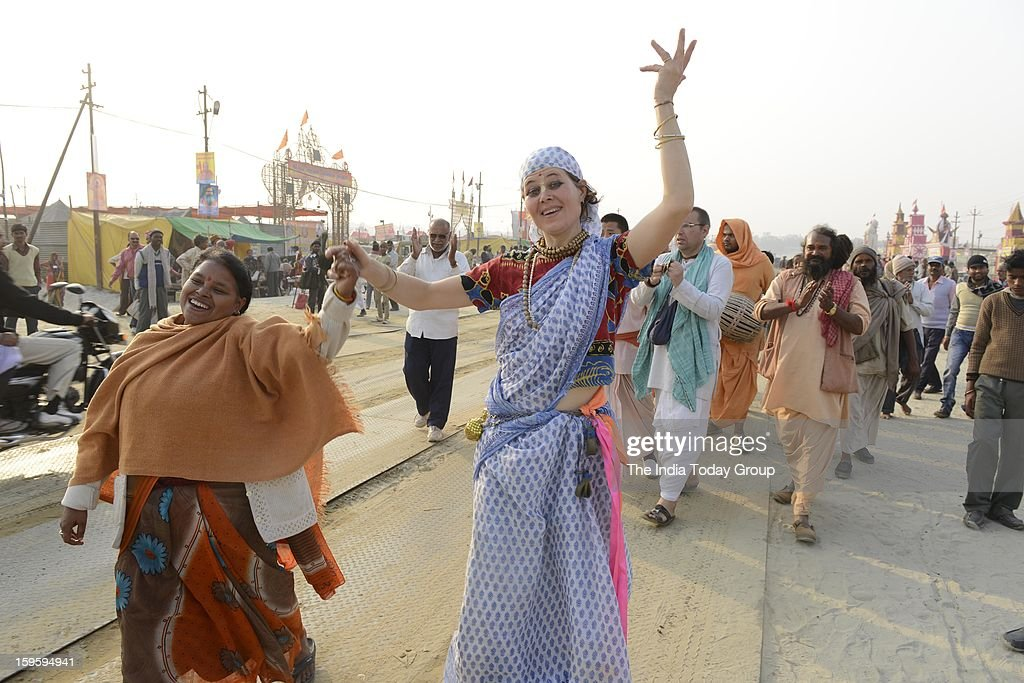 Devotees dance before they leave for a dip at Sangam, the confluence of the Rivers Ganges, Yamuna and mythical Saraswati.