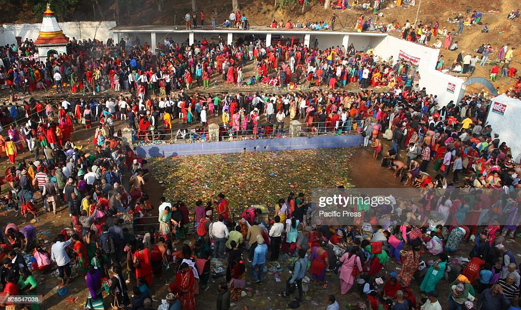 MATATIRTHA, KATHMANDU, NEPAL - : Devotees gathered to perform religious rituals and to take holy bath at a pond,stone taps in remembrance of their deceased mothers on Mata Tirtha Aunsi, or the Mother's Day.