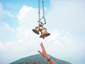 Two temple bells made of brass hanging through chain against cloudy sky and a devotee's hand trying to hit the bell. Place: Kali Ka Tibba, Chail, Himachal Pradesh.