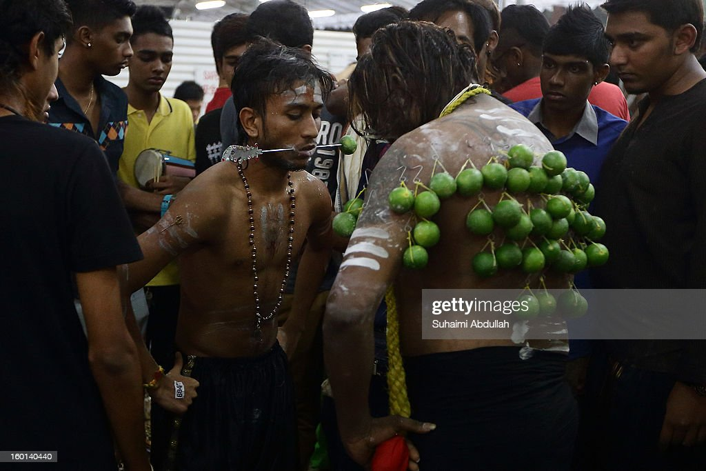 Devotees have their mouth and body pierced as they begin to prepare their Thaipusam procession at Sri Srinivasa Perumal Temple on January 27, 2013 in Singapore. Thaipusam is a Hindu festival celebrated on the full moon in the Tamil month of Thai. Devotees pray and make vows, when the prayers are answered they fulfill the vows by piercing parts of their body such as their cheeks, tongues, and backs before carrying a 'Kavadi' along a four kilometre route.
