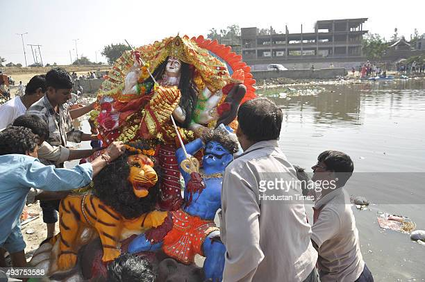 Devotees immerse Goddess Durga idols at Indira Priyadarshini Park Pond near Hindon River on October 22 2015 in Ghaziabad India Ghaziabad Development...