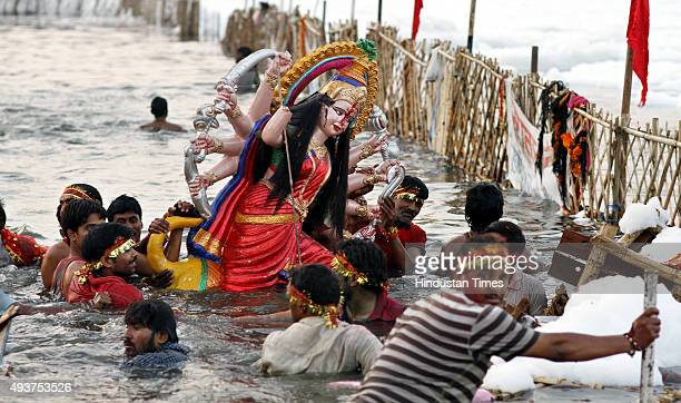 Devotees immersing idol of Goddess Durga in river Yamuna at Okhla Barrage on the occasion of Dashmi on October 22 2015 in New Delhi India Puja...