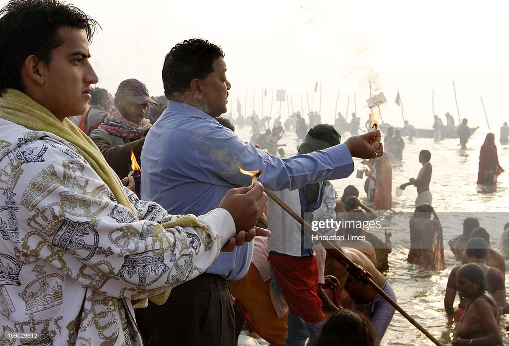 Devotees in the morning doing aarti at the bank of Sangam confluence of river Ganga, Yamnuna and mythical Saraswati on the occasion of Makar Sankranti on January 15, 2013 in Allahabad, India. Kumbh is World's biggest religious gathering, in which more than 100 million of Hindus and sikh devotees will take part over next 55 days. Apart from being pilgrimage of faith, salvation and hope for millions of devotees, it also serve as meeting ground for the vast spectrum of Indian religious and spiritual views.