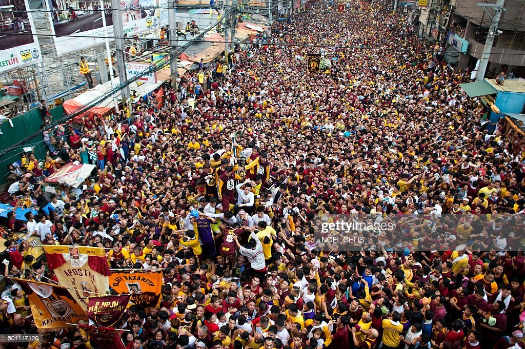Devotees join the annual procession with the religious icon of the Black Nazarene (C) in Manila on January 9, 2016. Barefoot men and women in search of miracles hurled themselves above huge crowds to touch a centuries-old icon of Jesus Christ as one of the world's largest Catholic festivals got under way. AFP PHOTO / NOEL CELIS / AFP / NOEL CELIS