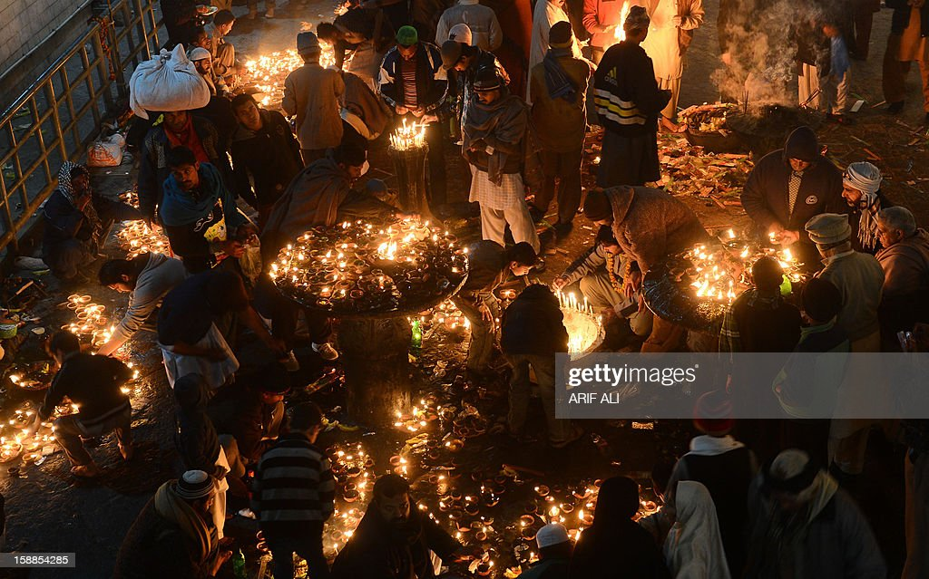 Devotees light candles at the shrine of Muslim Sufi Saint Data Ganj Bakhsh in Lahore on January 1, 2013. The three-day festival for Hazrat Ali Bin Usman, popularly known as Data Gunj Bakhsh, started with traditional zeal with a 'chaddar' laying ceremony and the distribution of communal milk at the shrine. AFP PHOTO/Arif ALI