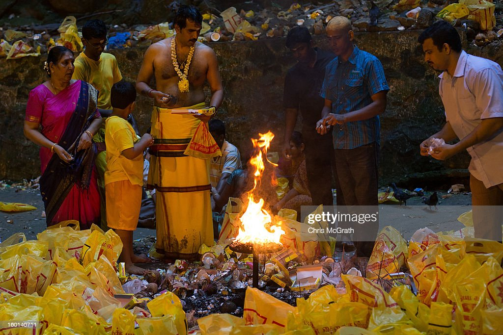 Devotees make offerings inside the Batu Caves during the Thaipusam procession on January 27, 2013 in Batu Caves, Malaysia. Thaipusam is a Hindu festival celebrated on the full moon in the Tamil month of Thai. The festival marks the birthday of Lord Muruga and also commemorates the day Hindu Goddess Parvati gave her son a lance to defeat the evil demon Soorapadamwhen. The festival sees devotees carry milk pots to seek forgivness and some will carry a 'Kavadi' many of which are attached via, strings, hooks, and skews pierced into the carriers skin.