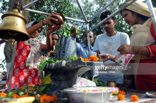 Devotees offer holy water of Ganga milk curd and honey to Shiva linga at Shiva Murti Temple on the first Monday of the holy month of Shravan on July...