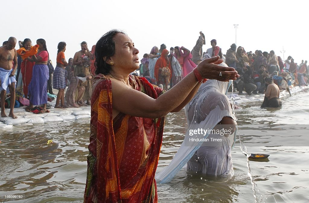 Devotees offers prayer after takes dip at banks of the Sangam ahead of Maha Kumbh festival on January 13, 2013 in Allahabad, India. The Kumbh Mela is mass Hindu pilgrimage that alternates between four places Allahabad, Haridwar, Ujjain and Nashik every three years. The current Kumbh Mela is scheduled to take place at Allahabad city in January and February 2013 and is expected to be attended by 60 million devotees.