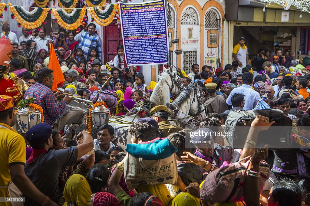 Devotees on their way to bath in Pushkar Lake merge with a procession, showcasing artists and children dressed as various Gods and Godesses, at a crossroad during the Pushkar Camel Fair in Pushkar, Rajasthan, India, on Sunday, Nov. 22, 2015. Throw together hundreds of thousands of rural Indians, colorful festivals and throngs of tourists and you get the annual Pushkar Fair. Photographer: Prashanth Vishwanathan/Bloomberg via Getty Images
