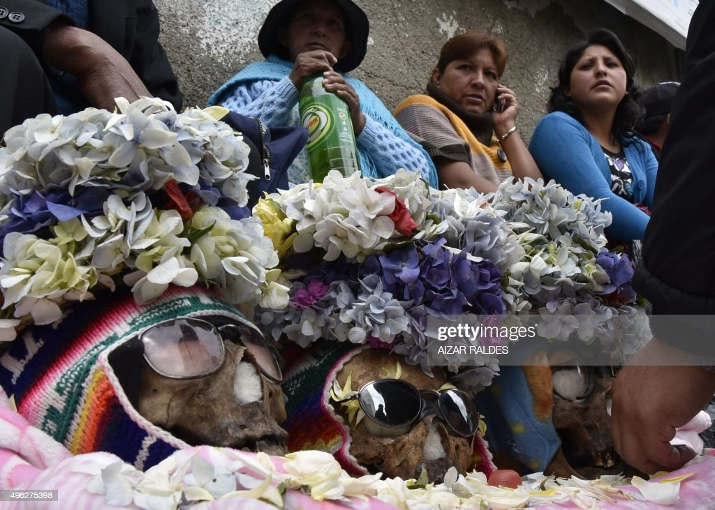 Devotees place candles and other offerings in front of human skulls at a cemetery in La Paz, on November 8, 2015, carrying a box with two human skulls to be blessed during the celebration of the Di...