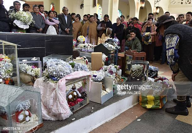 Devotees place candles and other offerings in front of human skulls at a cemetery in La Paz on November 8 carrying a box with two human skulls to be...
