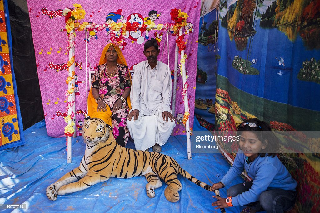 Devotees pose for a photograph at a portable photo studio prior to bathing in Pushkar Lake and praying at the Bramha Temple during the Pushkar Festival in Pushkar, Rajasthan, India, on Sunday, Nov. 22, 2015. Throw together hundreds of thousands of rural Indians, colorful festivals and throngs of tourists and you get the annual Pushkar Fair. Photographer: Prashanth Vishwanathan/Bloomberg via Getty Images