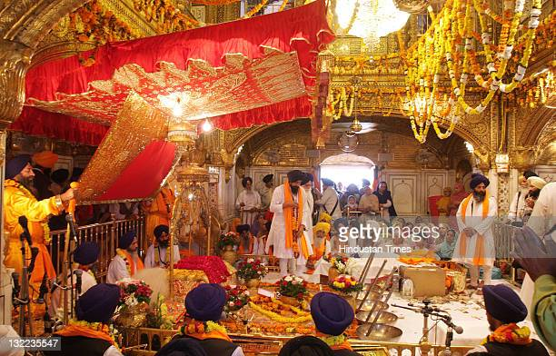 Devotees pray at the Sanctum Sanctorum of Harmandar Sahib decorated with flowers rare gold and diamond Jewelry as Jalau' a splendor show of symbolic...