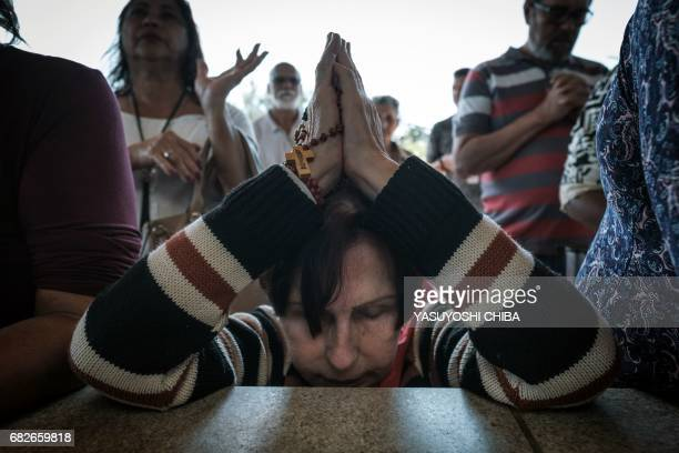 Devotees pray during the centenary mass marking the apparition of the Virgin Mary at the Chapel of the Apparitions in Rio de Janeiro Brazil on May 13...