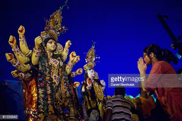 A devotees prays to an idol of Hindu goddess Durga before it being immersed into the river Ganges on the last day of the Durga Puja festival on...