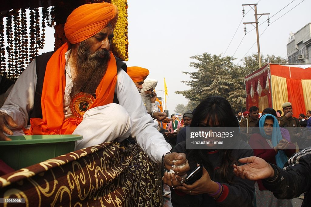 Devotees receiving blessed sweets during a religious procession on the occasion of Prakash Parv of the 10th Guru of Sikh Community Guru Gobind Singh at Sector 25, on January 13, 2013 in Noida, India.