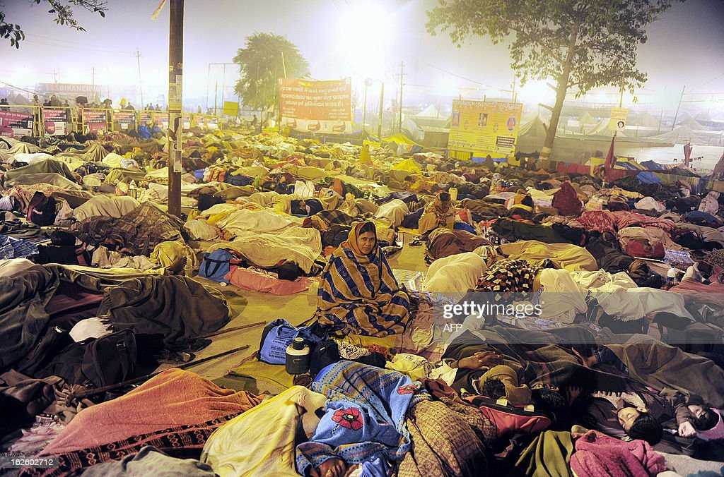 Devotees sleep on the bank of Sangam, the confluence of the rivers Ganges, Yamuna and mythical Saraswati during the Maha Kumbh festival in Allahabad on February 25, 2013. The Kumbh Mela in the town of Allahabad will see up to 100 million worshippers gather over 55 days to take a ritual bath in the holy waters, believed to cleanse sins and bestow blessings. AFP PHOTO/Sanjay KANOJIA