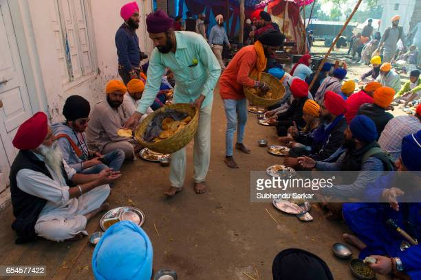 Devotees take food at a camp during Hola Mohalla festival Hola Mohalla is a threeday festival started by the tenth Sikh Guru Govind Singh for the...