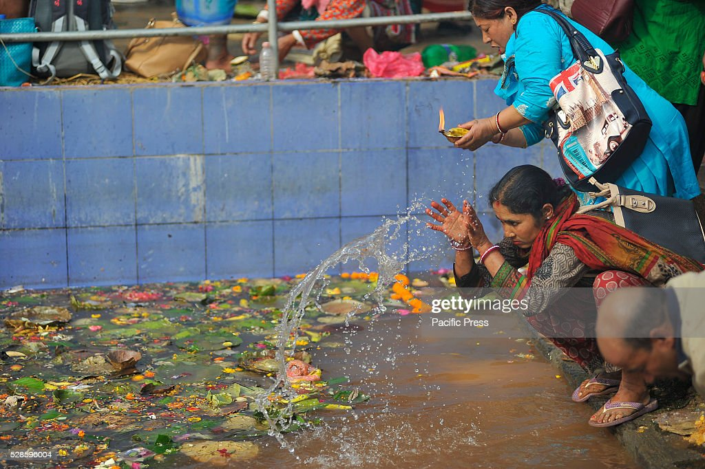 KATHMANDU, NEPAL, KATHMANDU, NP, NEPAL - : Devotees taking a holy bath during the Mother's Day celebration at Matatritha temple. Mother's day or Matatritha Ausi is celebrated on Baishak Krishna Ausi according to Lunar calendar. On this auspicious day, people pay homage to their mothers giving them gifts and foods including sweets and fruits.