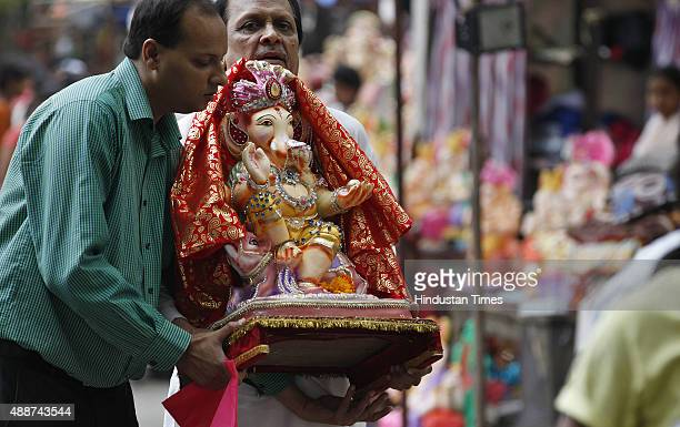 Devotees taking Lord Ganesha idols to their homes on the occasion of Ganesha Chaturthi festival near Sarojni Nagar on September 17 2015 in New Delhi...