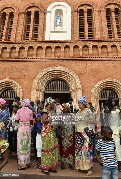 Devotees talk in front of Bangui's Cathedral on December 24 2013 after attending a 'midnight mass' in the afternoon of Christmas Eve because of the...