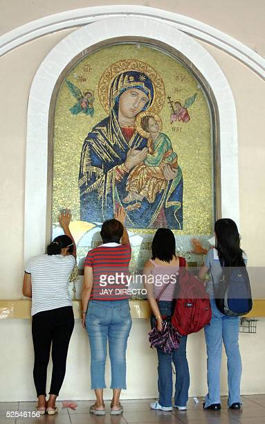 Devotees touch the image of the Virgin Mary at a cathedral in Manila 01 April 2005 as they pray for the Pope Pope John Paul II received the last...
