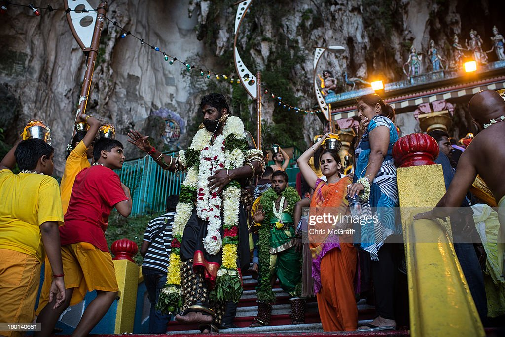 Devotees wait to enter the Batu Caves during the Thaipusam procession on January 27, 2013 in Batu Caves, Malaysia. Thaipusam is a Hindu festival celebrated on the full moon in the Tamil month of Thai. The festival marks the birthday of Lord Muruga and also commemorates the day Hindu Goddess Parvati gave her son a lance to defeat the evil demon Soorapadamwhen. The festival sees devotees carry milk pots to seek forgivness and some will carry a 'Kavadi' many of which are attached via, strings, hooks, and skews pierced into the carriers skin.