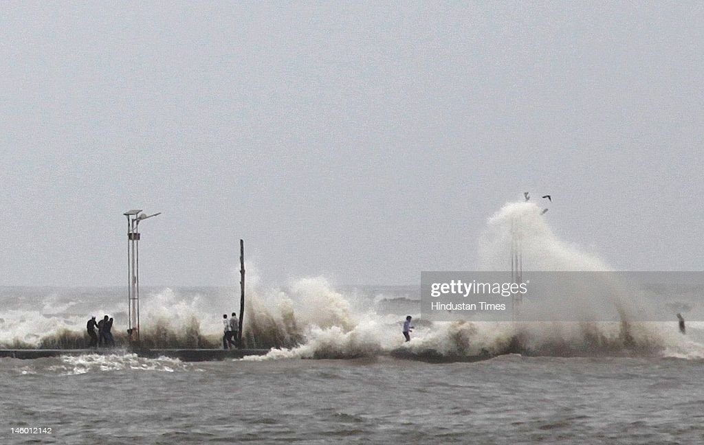 Devotees walk through breaking waves to reach the Dargah during the high tide at Baba Haji Ali on June 8, 2012 in Mumbai, India.