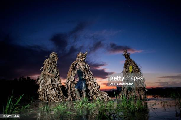 TOPSHOT Devotees wear costumes made of banana leaves as they head to church to attend mass as part of a religious festival in honor of St John the...