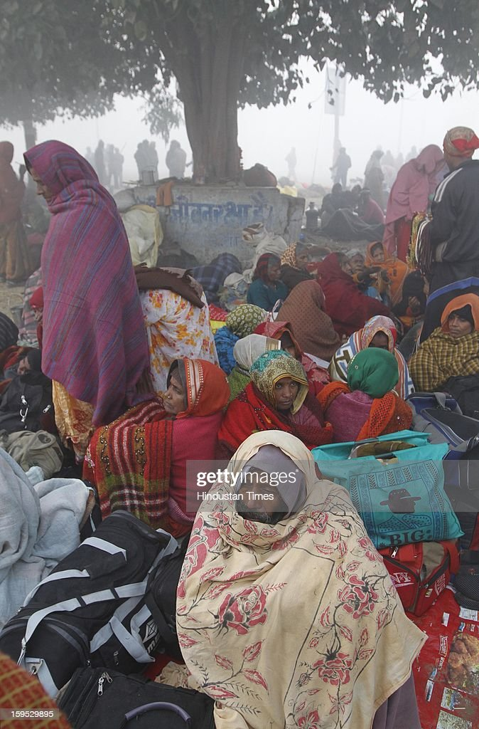 Devotees wrapped in warm cloths on chilly morning near the bank of Sangam confluence of river Ganga, Yamnuna and mythical Saraswati on the occasion of Makar Sankranti on January 15, 2013 in Allahabad, India. Kumbh is World's biggest religious gathering, in which more than 100 million of Hindus and sikh devotees will take part over next 55 days. Apart from being pilgrimage of faith, salvation and hope for millions of devotees, it also serve as meeting ground for the vast spectrum of Indian religious and spiritual views.