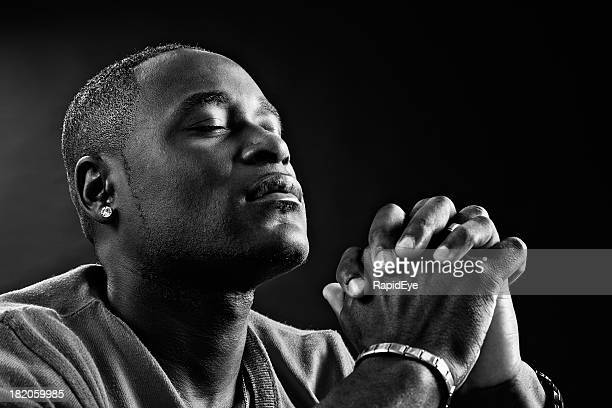 Devout African-American man praying fervently in black-and-white portrait