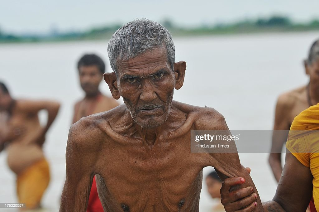 A devtoee is being helped to walk after taking a holy dip at Saryu ghat on August 28, 2013 in Ayodhya, India. Three days after Vishwa Hindu Parishad (VHP) field Parikarma attempt, Ayodhya saw a heavy presence of security personnel amid Janmashtmi celebrations. Old Man