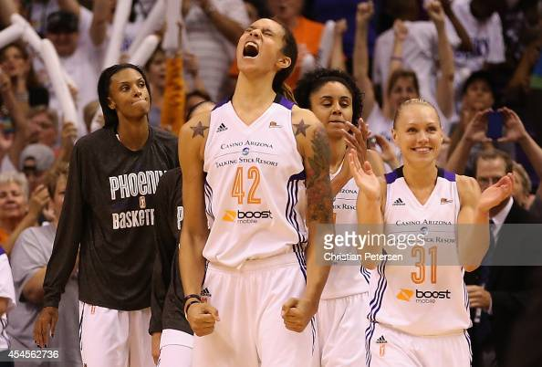 DeWanna Bonner Brittney Griner Candice Dupree and Erin Phillips of the Phoenix Mercury celebrate on the bench during the final moments before...