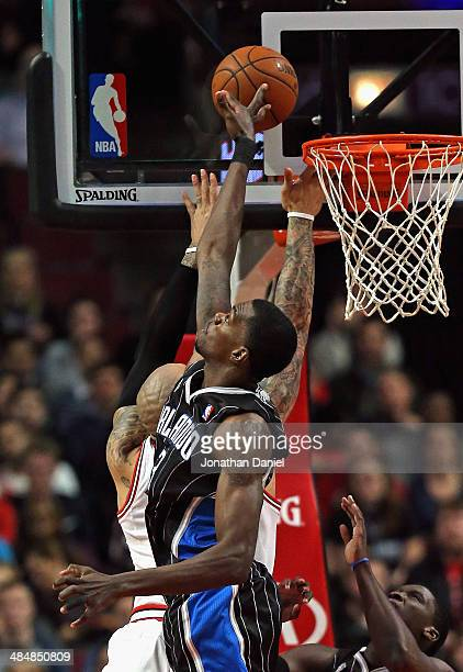 Dewayne Dadmon of the Orlando Magic blocks a shot by Carlos Boozer of the Chicago Bulls at the United Center on April 14 2014 in Chicago Illinois...