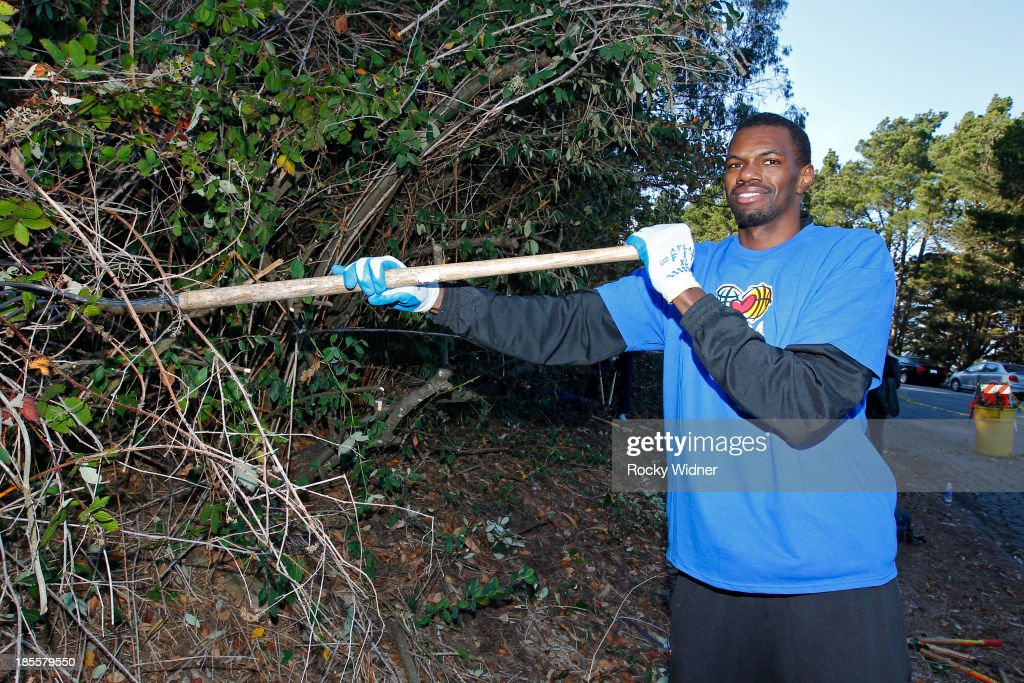 Dewayne Dedmon pitches in to help clean up McLaren park during Warriors Day Of Service as part of NBA Cares Week Of Service on October 21, 2013 in San Francisco, California.