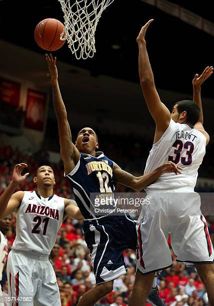 Dewayne Russell of the Northern Arizona Lumberjacks lays up a shot past Grant Jerrett of the Arizona Wildcats during the first half of the college...