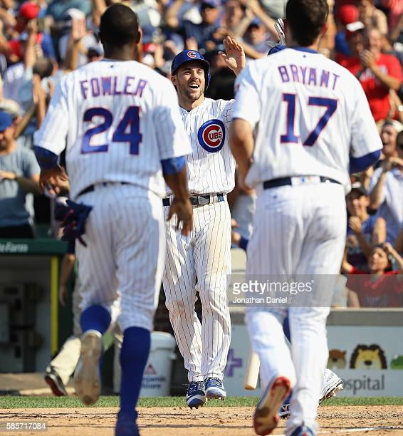 Dexter Fowler and Kris Bryant of the Chicago Cubs run up to congratulate Matt Szczur after he scored the game winning run on a wild pitch in the 9th...