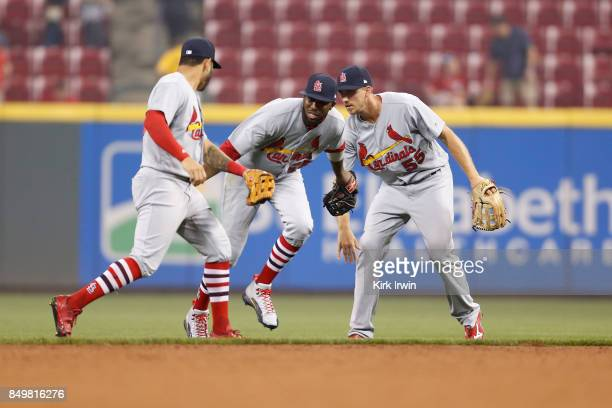 Dexter Fowler congratulates Tommy Pham and Stephen Piscotty of the St Louis Cardinals after defeating the Cincinnati Reds 87 in ten innings at Great...