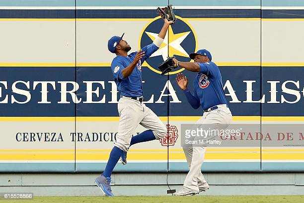 Dexter Fowler of the Chicago Cubs catches a fly ball and then crashes into teammate Jorge Soler in the second inning in game three of the National...