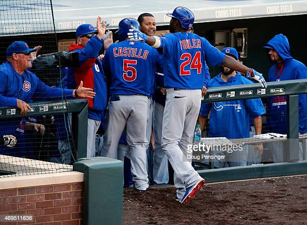 Dexter Fowler of the Chicago Cubs celebrates his game winning two run home run with Welington Castillo of the Chicago Cubs against the Colorado...