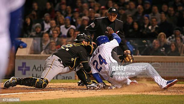 Dexter Fowler of the Chicago Cubs is tagged out at the plate in the 4th inning by Francisco Cervelli of the Pittsburgh Pirates at Wrigley Field on...