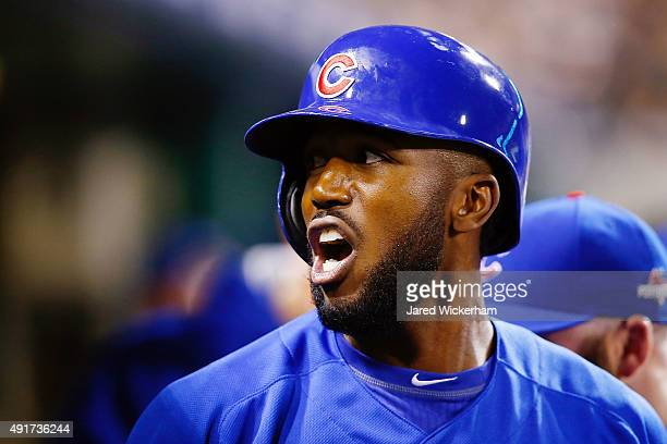 Dexter Fowler of the Chicago Cubs reacts in the dugout after scoring a run on an RBI single by Kyle Schwarber of the Chicago Cubs in the first inning...