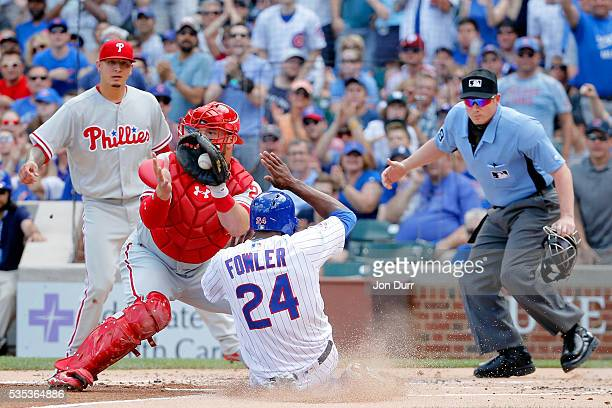 Dexter Fowler of the Chicago Cubs scores ahead of a tag by Cameron Rupp of the Philadelphia Phillies in the first inning on an RBI single by Anthony...