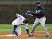 Dexter Fowler of the Chicago Cubs slides safely into second base with a double as Erick Aybar of the Atlanta Braves takes the throw during the eighth...