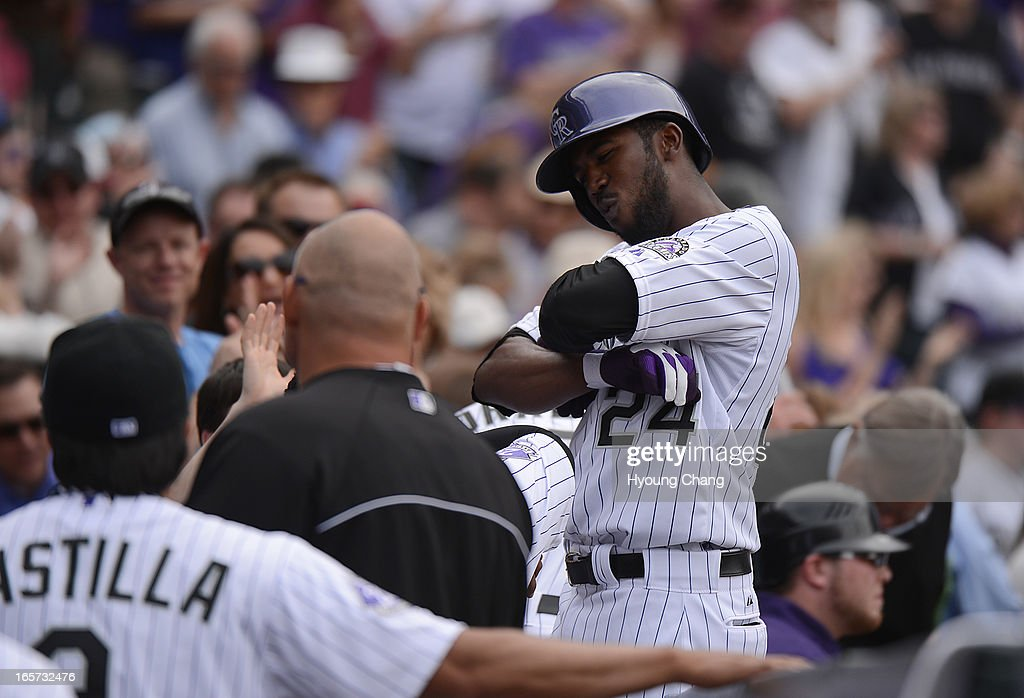 Dexter Fowler (24) of the Colorado Rockies celebrates when he returns to the dugout after hitting a home run to right in the fifth inning. The Colorado Rockies took on the San Diego Padres on Opening Day at Coors Field in Denver, Colorado.