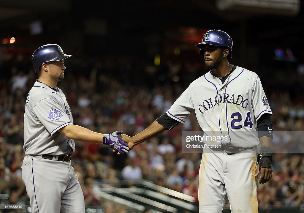 <a gi-track='captionPersonalityLinkClicked' href=/galleries/search?phrase=Dexter+Fowler&family=editorial&specificpeople=4949024 ng-click='$event.stopPropagation()'>Dexter Fowler</a> #24 of the Colorado Rockies high fives <a gi-track='captionPersonalityLinkClicked' href=/galleries/search?phrase=Michael+Cuddyer&family=editorial&specificpeople=208127 ng-click='$event.stopPropagation()'>Michael Cuddyer</a> #3 after scoring a seventh inning run against the Arizona Diamondbacks during the MLB game at Chase Field on April 27, 2013 in Phoenix, Arizona.