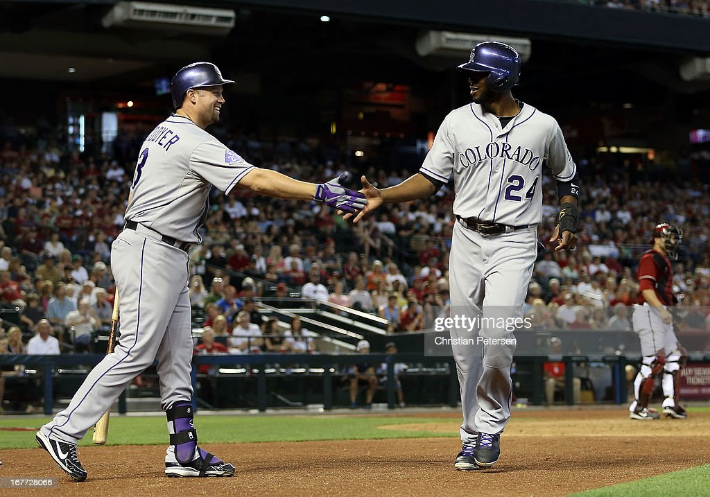 <a gi-track='captionPersonalityLinkClicked' href=/galleries/search?phrase=Dexter+Fowler&family=editorial&specificpeople=4949024 ng-click='$event.stopPropagation()'>Dexter Fowler</a> #24 of the Colorado Rockies high-fives <a gi-track='captionPersonalityLinkClicked' href=/galleries/search?phrase=Michael+Cuddyer&family=editorial&specificpeople=208127 ng-click='$event.stopPropagation()'>Michael Cuddyer</a> #3 after he scored a run against the Arizona Diamondbacks during the sixth inning of the MLB game at Chase Field on April 28, 2013 in Phoenix, Arizona.